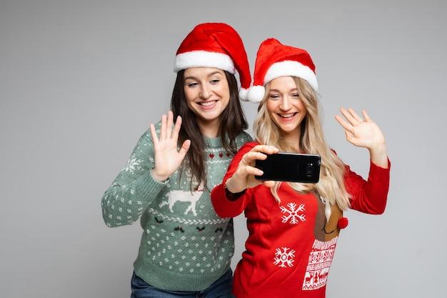 Le amiche attraenti in cappelli di natale rossi e bianchi posano per selfie