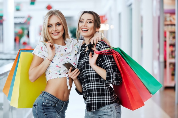 Attractive girls in shopping mall with bags