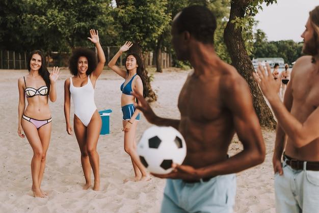 Attractive girls waving hands on summer beach
