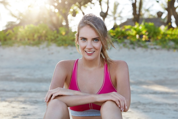 Attractive glad female jogger being motivated, has morning workout on sandy beach, rests alone, wears pink top. sportswoman involved in active lifestyle. people, fitness and outdoor exercises
