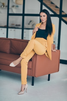 Attractive glamorous lady posing near the couch