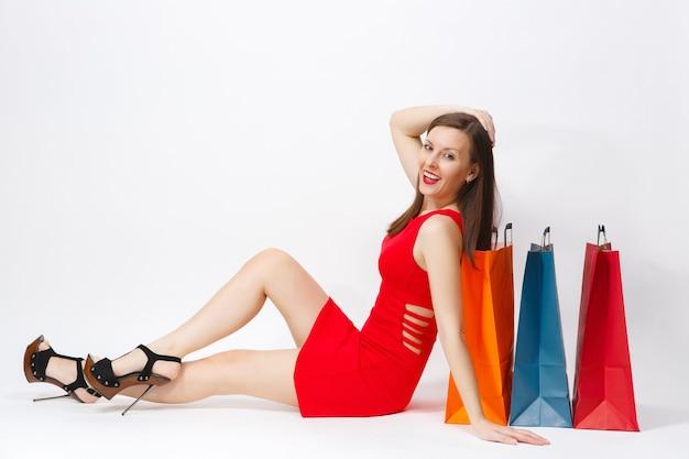 魅力的な魅力的な白人のファッショナブルな若い茶色の髪の女性は、白い背景で隔離の買い物の後の購入でマルチカラーのパケットに座っている赤いドレスを着ています。広告用のスペースをコピーします。