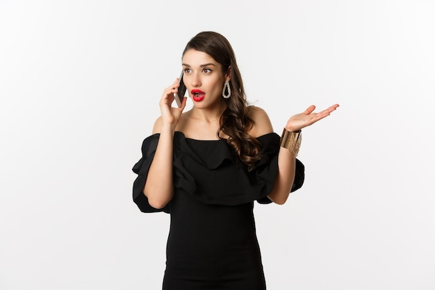 검은 드레스를 입은 매력적인 여성이 휴대전화로 통화하고 대화를 나누고 놀란 표정을 하고 흰색 배경 위에 서 있습니다.