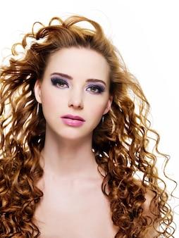 Привлекательная гламурная женщина с длинными красивыми волосами и стильным фиолетовым макияжем
