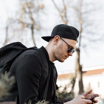 Привлекательный красивый молодой человек в стильных солнцезащитных очках в кепке в черной одежде с портфелем сидит и смотрит на мобильный телефон в солнечный день. модный турист парень отдыхает в городе. молодежная мода