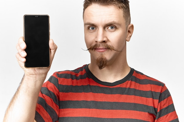 Attractive good looking young unshaven european male dressed in striped t-shirt holding generic black mobile phone with blank display with copyspace for your text, template or advertisement