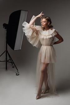 춤 위치에 흰색 바탕에 서있는 이브닝 드레스에 매력적인 화려한 여자.