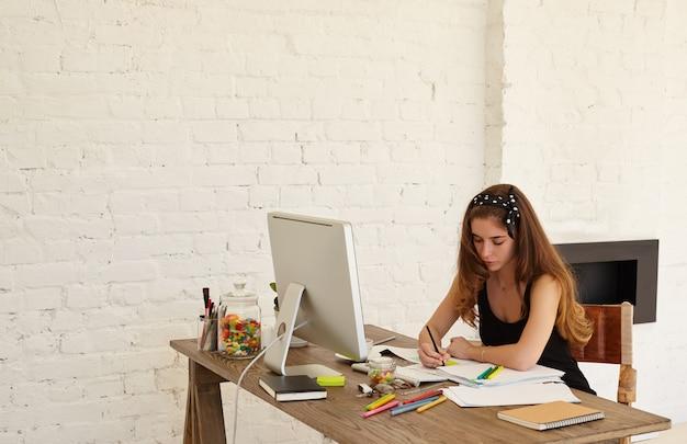 Привлекательная женщина-графический дизайнер рисует эскизы нового логотипа для стоматологической клиники, сидя за столом с компьютером, документами и цветными канцелярскими принадлежностями. скопируйте космическую стену для рекламного контента или текста
