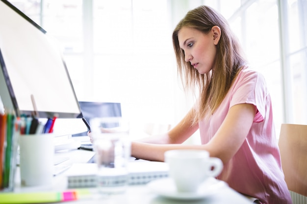 Attractive graphic designer working at desk