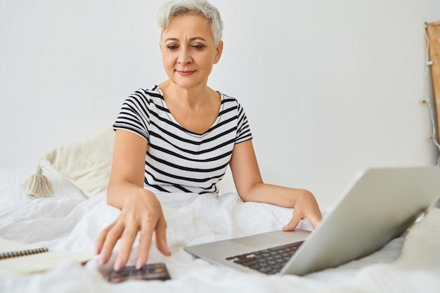Attraente donna di affari anziana dai capelli grigi che lavora in remoto direttamente dalla camera da letto, seduto sul letto con il computer portatile, utilizzando la calcolatrice, gestendo le finanze, avendo un'espressione felice fiduciosa