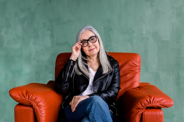 Attractive gray haired lady in black leather jacket and fashionable eyeglasses, sitting in red armchair on green background, looking at camera with smile