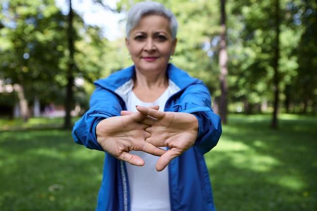 Attraente donna caucasica matura dai capelli grigi che indossa giacca blu protesa, allungando le braccia e le mani, facendo routine di riscaldamento durante l'allenamento all'aperto al mattino. messa a fuoco selettiva sui palmi