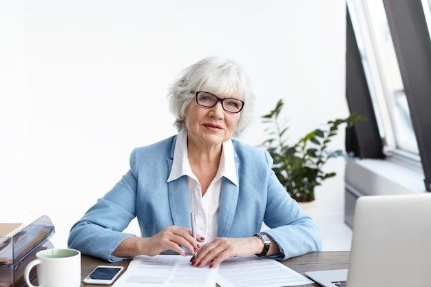 매력적인 회색 머리 수석 사업가 유행 양복과 그녀의 사무실에서 일하는 안경, 열린 노트북 및 서류와 함께 책상에 앉아 재무 문서 작성, 심각한 표정을 갖는