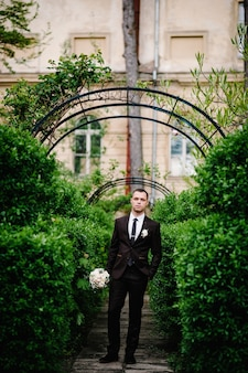 The attractive groom in a suit and tie with wedding bouquet flowers, and a boutonniere or buttonhole on the jacket is standing on the background arch with greenery in park.