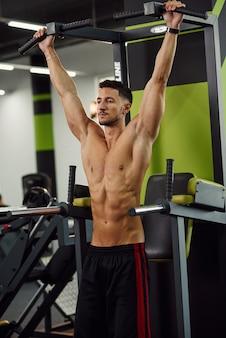 현대적인 체육관에서 훈련하는 동안 크로스바에 풀업을하고 매력적인 남자. 총을 닫습니다.