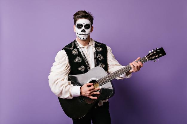 メキシコのカーニバルの衣装を着た魅力的な男がギターを弾きます。孤立した壁に黒髪のクローズアップの肖像画。