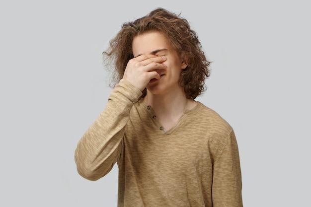顔の手のひらジェスチャー、笑い、恥ずかしさを感じているスタイリッシュなtシャツの魅力的な男。痛み、恥、悲しみ、喪失、恥ずかしさ、またはストレスのために目を覆っている感情的な若い男