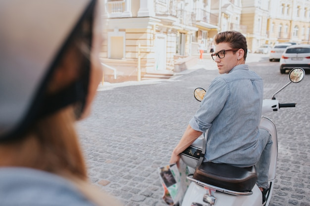 Attractive guy is sitting on motorcycle and looking back at woman