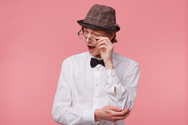 Attractive guy isolated on pink background, dressed in white shirt, hat and black bow tie pretends to lower the glasses and winks happily with approval