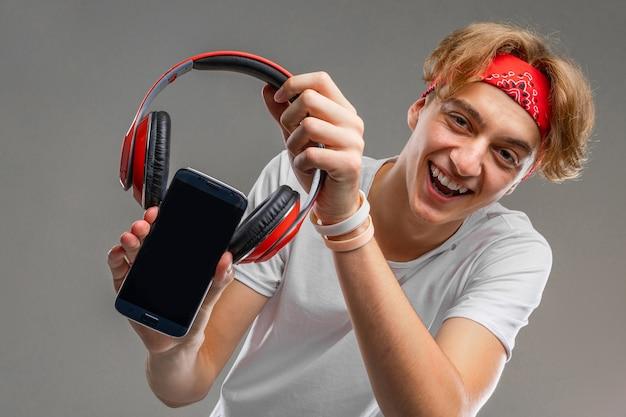 魅力的な男は電話にヘッドフォンを置きました