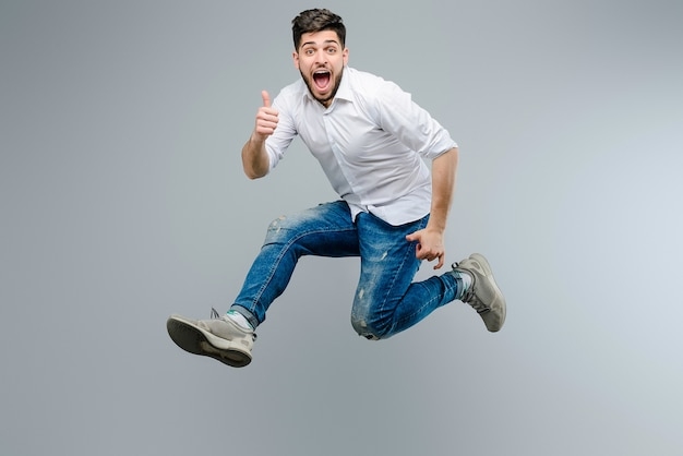 Attractive guy in white shirt jumping and showing thumbs up isolated over gray background