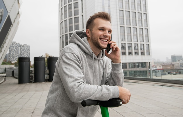 あごひげを生やした魅力的な男が、電気自動車を借りる便利さについて電話で友人に話します。環境にやさしい輸送コンセプト。カジュアルな服装。背景のアパートのブロック。