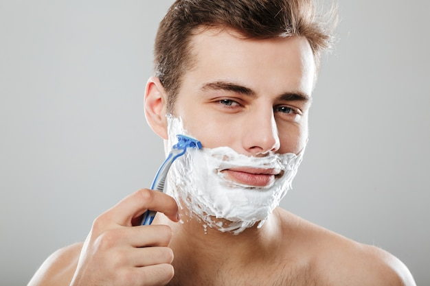 Attractive guy with dark short hair shaving his face with razor and gel or cream being isolated  over grey wall close up