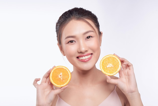 Attractive half-naked asian woman amiling while holding orange slices near her face