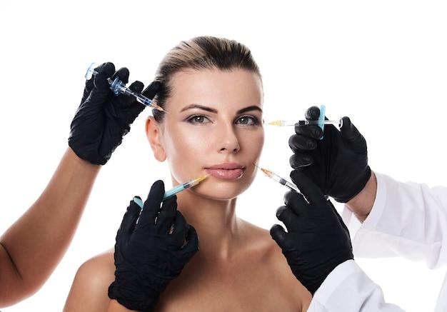 魅力的な半裸の女性と彼女の顔の近くに注射器を保持している医療用手袋の手。コピースペースで白に分離