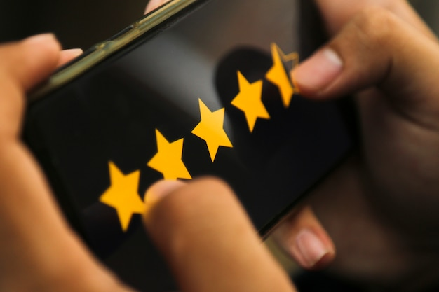 Привлекательные руки, дающие четыре целых пять звездных оценок на смартфоне