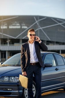 Attractive handsome businessman with diplomat talking on smartphone near the car