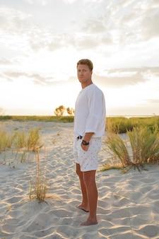ビーチに立っている魅力的なハンサムなヨーロッパ人。