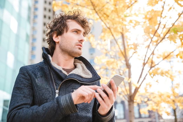 Attractive handsome pencive thoughtful curly man holding cellphone and waiting in the street of the city in autumn