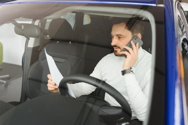 車でモバイルのスマートフォンを使用して魅力的なハンサムな青年実業家。