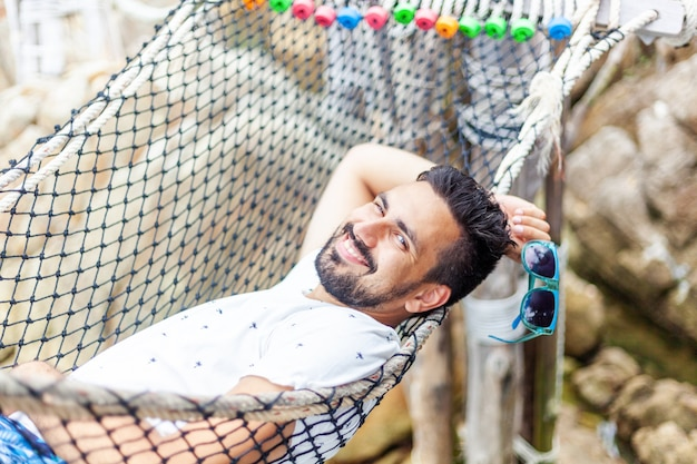Attractive handsome young latin brunette man in sunglasses with a beard on a hammock on vacation
