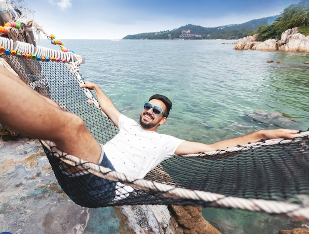 Attractive handsome young latin brunette man with a beard on a hammock on vacation