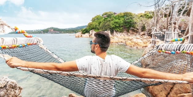 Attractive handsome young latino brunette man with a beard on a hammock on vacation