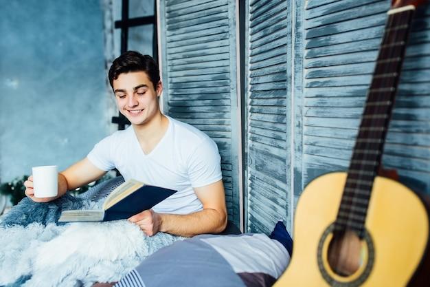 魅力的でハンサムな若い男がベッドに上半身裸で横たわり、本を読みながらコーヒーやティーカップを持っています