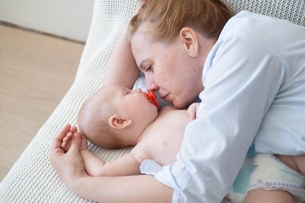 작은 아기와 함께 누워 매력적인 행복 성인 어머니. 육아 및 출산 개념. 행복한 가족. 집에서 즐기는. 사랑.