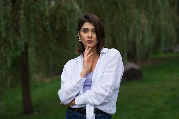 自然の公園でポーズをとる魅力的で幸せでスタイリッシュなブルネットの白人の女の子。ライフスタイルとファッションのコンセプト。