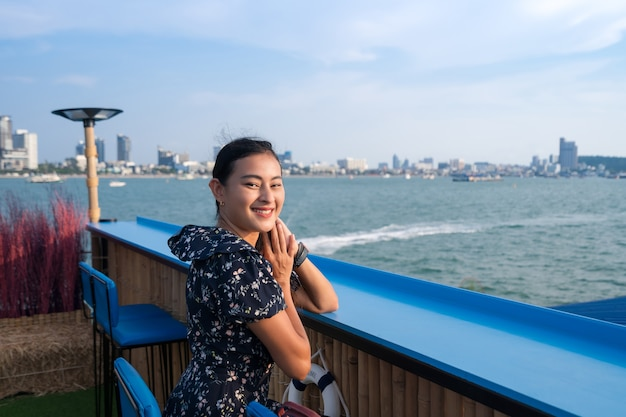 Attractive happy asian woman sit at table bar floating on sea with city view in evening, pattaya city seaside, thailand