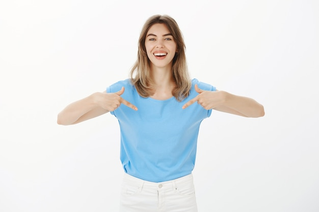 Attractive happy blond woman pointing at your logo, showing company banner