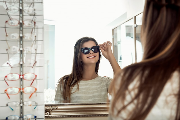 Attractive happy brunette woman looking in mirror while trying on sunglasses in optician store