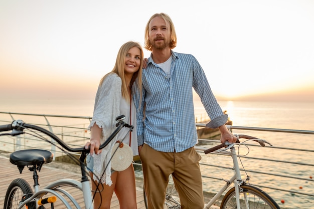 Attractive happy couple of friends traveling in summer on bicycles, man and woman with blond hair boho hipster style fashion having fun together, walking by the sea on vacation