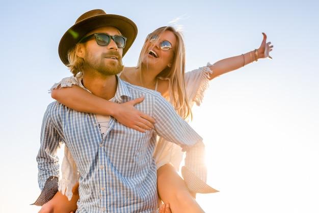 夏に海、男と女のサングラスをかけて旅行を笑って魅力的な幸せなカップル