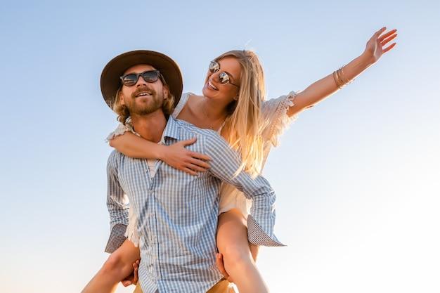 海で夏の旅を笑って笑う魅力的な幸せなカップル