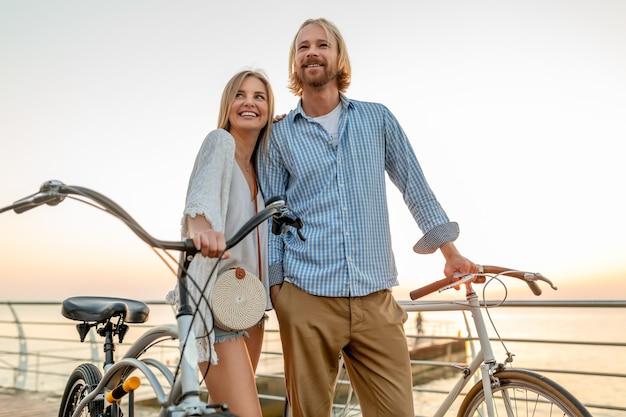 夏に自転車で旅行する友人の魅力的な幸せなカップル、男と女のブロンドの髪自由奔放に生きるヒップスタースタイルのファッションを一緒に楽しんで、リゾート都市の海沿いを歩く