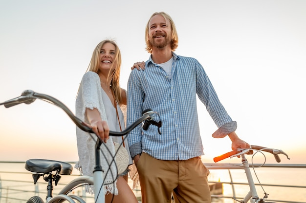 Привлекательная счастливая пара друзей, путешествующих летом на велосипедах, мужчина и женщина со светлыми волосами в стиле хипстера в стиле бохо, весело проводящие время вместе, гуляя по берегу моря в курортном городе
