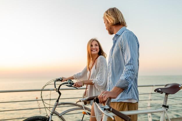 Привлекательная счастливая пара друзей, путешествующих летом на велосипедах, мужчина и женщина со светлыми волосами в стиле хипстера в стиле бохо, весело проводящие время вместе, гуляя по морю в отпуске
