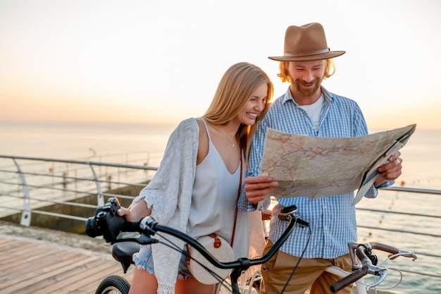 Привлекательная счастливая пара друзей, путешествующих летом на велосипедах, мужчина и женщина со светлыми волосами в стиле хипстера в стиле бохо, весело проводящие время вместе